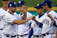 Round Rock Express third baseman Kevin Kouzmanoff #3 is greeted by his teammates before the Pacific Coast League baseball game against the Oklahoma City Redhawks on April 3, 2014 at the Dell Diamond in Round Rock, Texas. The Redhawks defeated the Express 7-6 in the season opener for both teams. (Andrew Woolley/Four Seam Images)