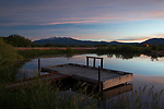 Idaho, South central, Camas County, Fairfield, A kids fishing pond in the pre-dawn light  reflecting in the calm water with Soldier Mountains distant.