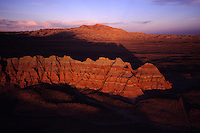 "Honeycomb Buttes catch early morning light in the Red Desert, a wilderness study area. ..Wyoming's Red Desert was included in The Wilderness Society's list of ""15 Most Endangered Wildlands"" because of massive oil and gas development in the wild heart of this 600,000 national treasure. The desert's stunning rainbow colored hoo-doos, towering buttes and prehistoric rock art, define this rich landscape and provide a truly wild ""home on the range"" for the largest migratory game herd in the lower 48 states - over 50,000 pronghorn antelope in addition to a rare desert elk herd..."