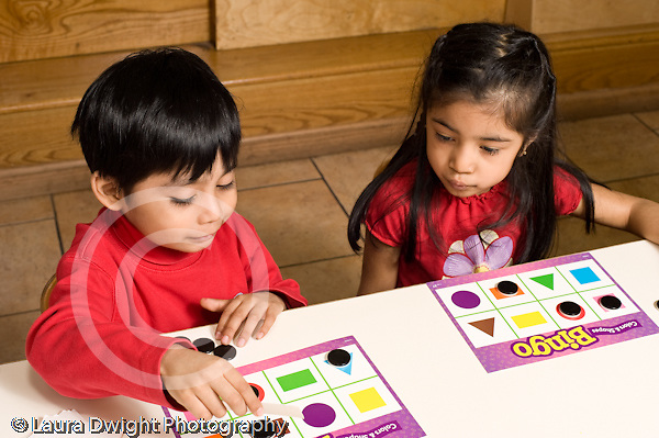 Education Preschool 3-5 year olds board game boy and girl playing shapes bingo horizontal
