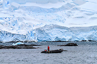 A zodiac cruises through Mikkelsen Harbor on Trinity Island near the Antarctic Peninsula.