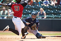Charleston RiverDogs catcher Eduardo Navas (20) prepares to apply a tag to Sherten Apostel (13) of the Hickory Crawdads as he approaches home plate at L.P. Frans Stadium on May 13, 2019 in Hickory, North Carolina. The Crawdads defeated the RiverDogs 7-5. (Brian Westerholt/Four Seam Images)