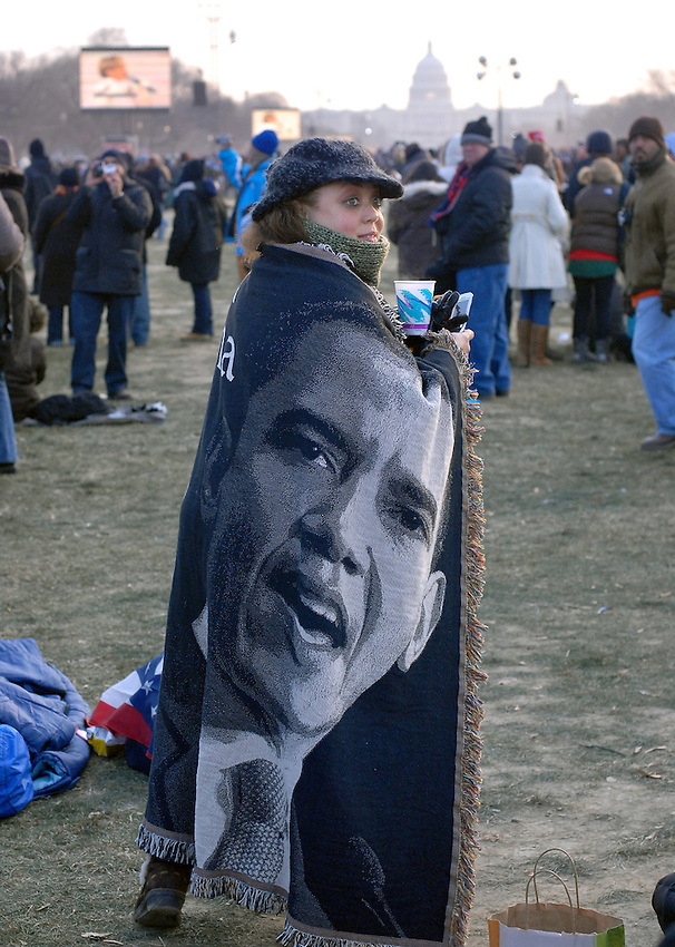A woman protects herself from the cold with a Barack Obama blanket on the National Mall before inauguration ceremonies for President Barack Obama in Washington, D.C., Tuesday, Jan. 20, 2009. (Ryan Rayburn/pressphotointl.com)