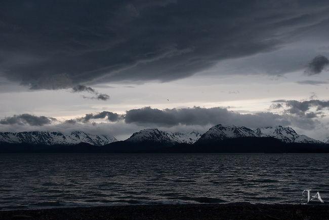 Threatening sky in Homer Alaska looking toward Kachemak Bay. Taken from the Southernmost part of Homer Spit. A lone Seagull flys in the distance.