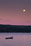 Full moon setting in purple sky at dawn over lone boat in calm water, Tomales Bay, Marin County, California