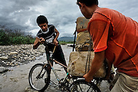 Smugglers push a bicycle loaded with gasoline barrels on the shore of the river Tachira on the Colombia-Venezuela border, 3 May 2006. Venezuelan gasoline, being 20 times cheaper than in Colombia, is the most wanted smuggling item, followed by food and car parts, while reputable Colombian clothing flow to Venezuela. There are about 25,000 barrels of gasoline crossing illegally the Venezuelan border every day. The risky contraband smuggling, especially during the rainy season when the river rises, makes a living to hundreds of poor families in communities on both sides of the frontier.