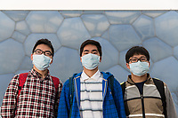 """Students Liu (21), Xu (22) and Han (21) stand near the Olympic Swimming Center during a visit to Beijing from southern China. """"We never wore a mask before. After we arrived in Beijing we bought it"""", explains Liu. """"The air quality is not good"""", continues Xu. """"More and more people pay attention to this. We should pay more attention to this problem. Every person has to start the change.""""  PM2.5 reading - 218 - Very Unhealthy"""
