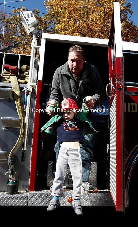 Middlebury, CT- 20 October 2013-102013CM10- Mark Stein, of Middlebury helps his son Chase Stein 2, off Engine 2 with the Middlebury Volunteer Fire Department, returning to the station after giving a ride to children and adults during an open house in Middlebury Sunday afternoon.   The department gave a tour of the fire house, put on demonstrations including a vehicle extraction and extinguished a mock vehicle fire. Christopher Massa Republican-American