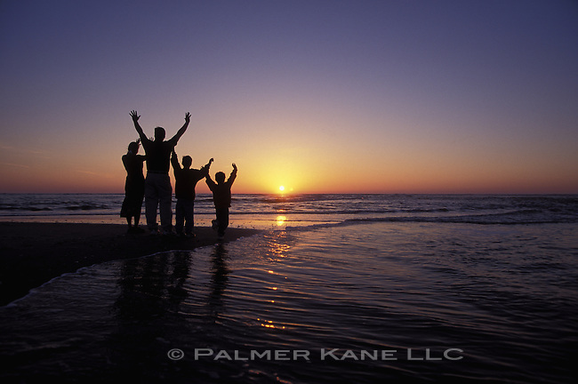 SILLO OF FAMILY ON BEACH AT SUNRISE, RAISING THEIR HANDS TO THE SUN. CAPE FEAR, BALD HEAD ISLAND, N. CAROLINA USA