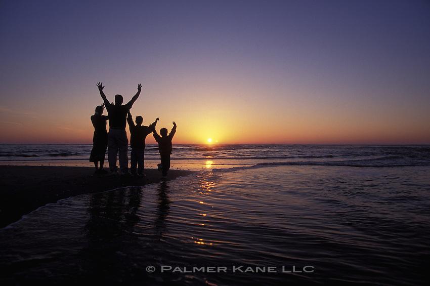 SILLO OF FAMILY ON BEACH AT SUNRISE, RAISING THEIR HANDS TO THE SUN. CAPE FEAR, BALD HEAD ISLAND, N. CAROLINA USA