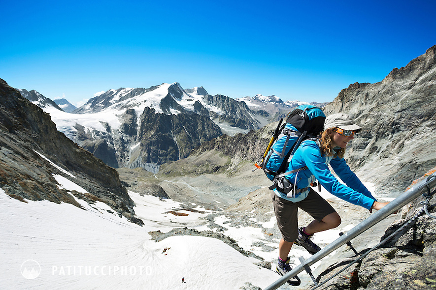 A woman hiker climbing a ladder to the Bertol Hut on the fourth day of the Chamonix to Zermatt Glacier Haute Route