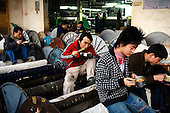 """Denim textile workers eat while sitting on giant spindles at a factory in Zhongshan city, China. .This picture is part of a photo and text story on blue jeans production in China by Justin Jin. .China, the """"factory of the world"""", is now also the major producer for blue jeans. To meet production demand, thousands of workers sweat through the night scrubbing, spraying and tearing trousers to create their rugged look. .At dawn, workers bundle the garment off to another factory for packaging and shipping around the world..The workers are among the 200 million migrant labourers criss-crossing China.looking for a better life, at the same time building their country into a.mighty industrial power."""