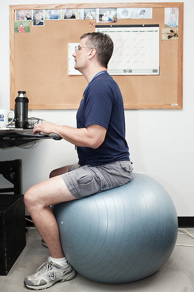 July 29, 2011. Cary, NC..Denny Cook sits on an exercise ball in his office. After suffering back injuries, he finds it easier to use the ball as a chair.. Profile of SAS, a software company that has many amenities for its employees.