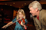 Morgan McAdams,6, tries out the violin while her father Mark watches at the Houston Symphony League's annual Magical Musical Morning event at the Houstonian Saturday Dec. 12,2009.(Dave Rossman/For the Chronicle)