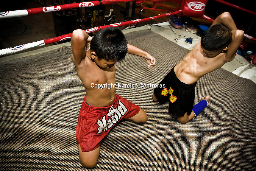 Luk Mi 10 years old (right) and Hiu Kiho 10 years old (left) a young kid fighters, are training at one of the street gyms in Bangkok. The gym at the Sam Soen neighborhood is managed by At, who is hosting and training over 10 kids an average. Over though is banned by law, in the streets of Thailand thousands of kids are training daily to attain a dream, become a Muay Thai champions one day, getting wealth and fame to leave out poverty and lackness instead. One by thousand each shall get it, meanwhile mostly of them will go keeping on the way to be someone.
