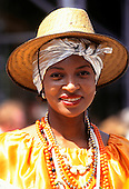 Salvador, Bahia, Brazil. Smiling Bahiana woman wearing yellow dress with bead and shell necklaces and a straw hat.