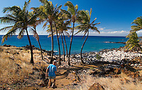 Man walking to shoreline at ancient Hawaiian village with palms at Lapakahi State Historical Park, Big Island of Hawaii