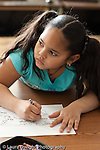 Education Elementary school Grade 2 portrait of female student in class looking to side coloring geograpic map vertical