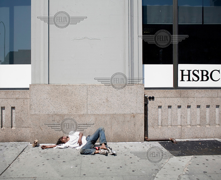A young man lies passed out on a sidewalk next to a bank in Chelsea, New York City.