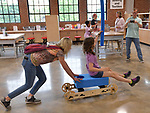 "Fourth grade teacher Mary McDevitt (left) pushes student Daisy Lazaroff, 10, on a wheeled ""rig-a-ma-jig"" she helped put together at the ""Design Small, Build Big"" exhibit. The wheeled scooter appears to be the marriage between giant lego blocks and an erector set. The Magic House had two fourth-grade classes from the New City School visit their new permanent satellite location at 5127 Delmar Boulevard in St. Louis, MO on Wednesday May 23, 2019.<br /> Photo by Tim Vizer"