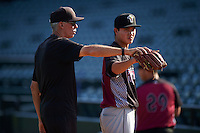 Wisconsin Timber Rattlers pitching coach Gary Lucas (25) works with pitcher Kodi Medeiros (16) before a game against the Peoria Chiefs on August 21, 2015 at Dozer Park in Peoria, Illinois.  Wisconsin defeated Peoria 2-1.  (Mike Janes/Four Seam Images)