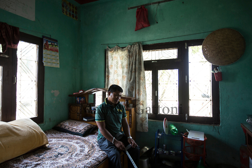 Nepal - Meghauli - Bhupendra Malla Thakuri, 32, in his house in Meghauli, in the Central district of Chitwan. In June 2011 Thakuri received a permanent injury in a car accident while he was working as a driver in Qatar. It took him more than two years of legal battles to receive a compensation of 33,500 USD. During this period, Thakuri didn't receive any salary, surviving thanks to the help of his co-workers, who secretly fed and hosted him in their labour camp. Thakuri will never be able to walk properly again, tend his field or do any manual job. He is now thinking about setting up a small shop in Meghauli, but he is afraid this will not be enough to feed his wife and three children.
