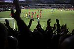 Home fans at Broadhurst Park, Manchester, the new home of FC United of Manchester applauding the opposition at the conclusion of the club's match against Benfica, champions of Portugal, which marked the official opening of their new stadium. FC United Manchester were formed in 2005 by fans disillusioned by the takeover of Manchester United by the Glazer family from America. The club gained several promotions and played in National League North in the 2015-16 season, but lost this match 1-0.