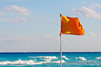 Yellow lifeguard flag over turquoise blue ocean surf