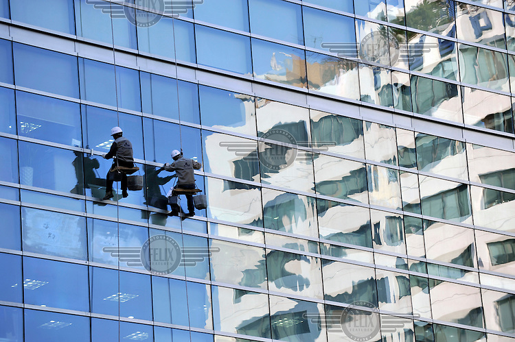 Workers clean office windows in central Seoul.