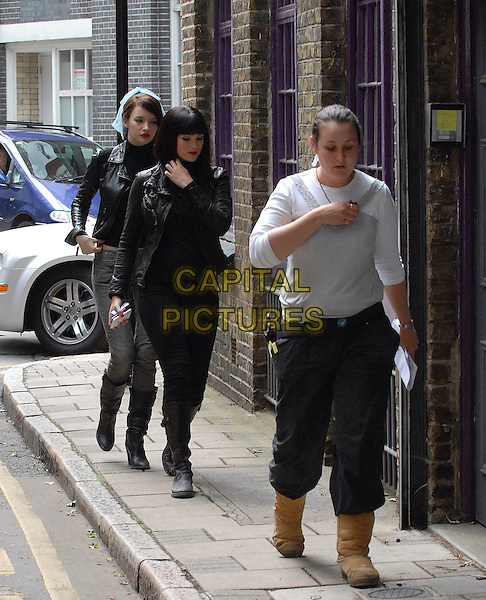 """TALULAH RILEY & GEMMA ARTERTON.On the set of """"St Trinian's: The Legend of Fritton's Gold"""" (St Trinian's 2), London, England..July 8th, 2009.full length tallulah walking black leather jacket jeans denim boots top.CAP/IA.©Ian Allis/Capital Pictures."""