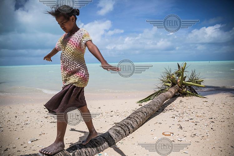 Tiiria, 11, walking on a fallen coconut treeon the beach near her family house in Teaoraereke village.