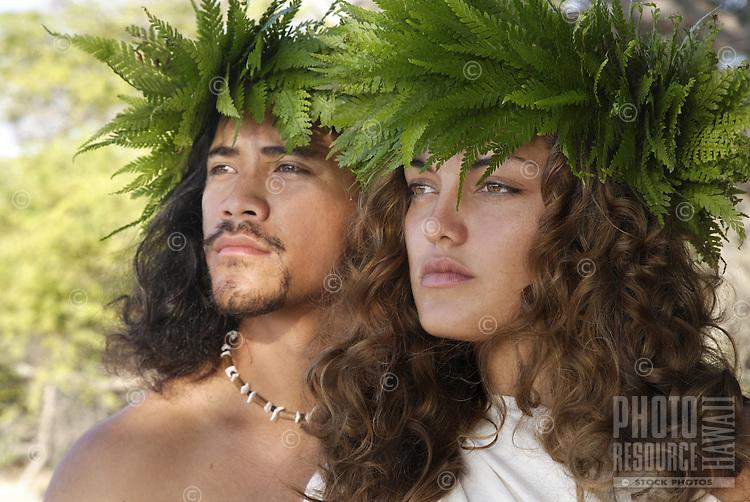 Male (kane) and female (wahine) hula dancers deep in thought, wearing palapalai fern head lei, headshot.