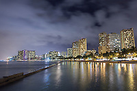 The Waikiki skyline at night, with lights from hotels reflecting off the water, as seen from Kuhi'o Beach Park (a.k.a. The Ponds) in Waikiki, O'ahu.