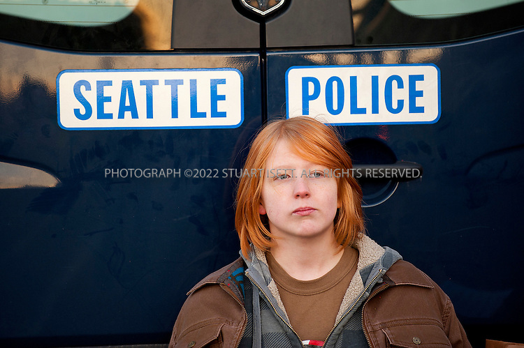 12/12/2011--Seattle, WA..Occupy Seattle, an off-shoot of the Occupy Wall Street movement, organized a protest Monday, December 12th, to block the Port of Seattle as part of a West Coast coordinated action in San Diego, Los Angeles, Oakland, Portland, Tacoma, Vancouver, B.C., and Houston. The 'Port shut down' protest was not endorsed by any of the maritime unions including the International Longshore and Warehouse Union (ILWU) which has been in a bitter labor despite in Westport, Washington...Here: a young protester waits to be taken in a police van after being arrested by Seattle police at one of the entrances to the Port of Seattle the protesters were attempting to block...©2011 Stuart Isett. All rights reserved.