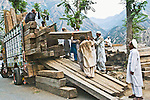 Pakistani men loading lumber onto a cargo transport truck manually along the Karakoram highway in Pakistan