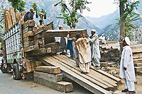 Pakistani men loading lumber onto a cargo transport truck manually along the Karakoram highway in Pakistan