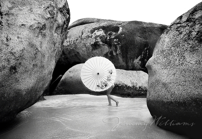 A woman holds up her parasol while walking between large boulders in carribean waters