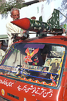 © Piers Benatar/Panos Pictures..Rawalpindi, Pakistan. 2001...Pakistan is very proud of its status as the only Muslim nuclear power, a pride which manifests itself in sculptures, murals and merchandising paraphernalia depicting its Ghauri and Shaheen missiles. Here, a man is mounting a model nuclear missile onto his car.