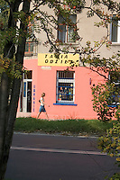 Woman walking along clothing store sklep on Lutomierska Street. Balucki District Lodz Central Poland