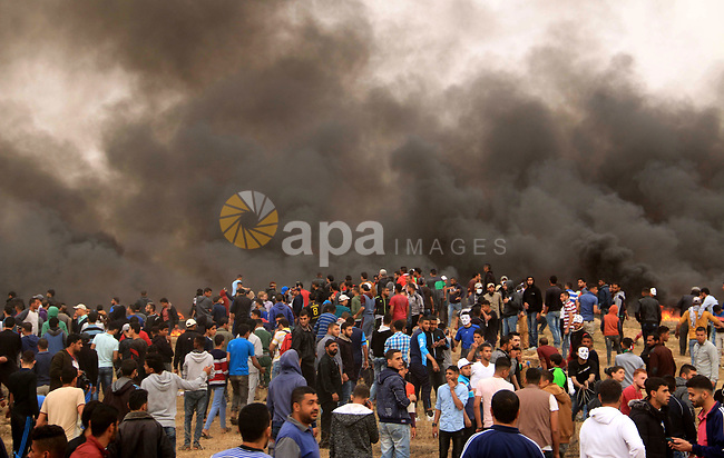 Palestinian protesters burn tires during clashes with Israeli security forces at tents protest at the Israel-Gaza border where Palestinians demand the right to return to their homeland, at the Israel-Gaza border, in Bureij in the cetner of Gaza strip on April 20, 2018. Photo by Mahmoud Khattab