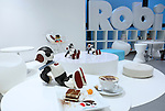 """A communication robot called """"Robi"""" is seated behind a cafe latte and a tiramisu inspired by the robot during a press preview for """"Robi cafe"""" where visitors can interact with the robots while enjoying meals and drinks in Tokyo, Thursday, January 15, 2015. The robot can be built by assembling parts sent along with a weekly magazine by Deagostini. The cafe will open from January 16 until February 8. (Photo by Yuriko Nakao/AFLO)"""