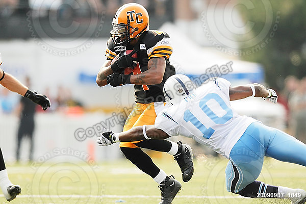 September 7, 2009; Hamilton, ON, CAN; Hamilton Tiger-Cats wide receiver Arland Bruce III (4) breaks a tackle attempt by Toronto Argonauts linebacker Willie Pile (10). CFL football - the Labour Day Classic - Toronto Argonauts vs. Hamilton Tiger-Cats at Ivor Wynne Stadium. The Tiger-Cats defeated the Argos 34-15. Mandatory Credit: Ron Scheffler.