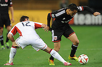 Washington, D.C.- March 29, 2014. Fabian Espindola (9) of D.C. United goes against Andy Dorman (12) of the New England Revolution.  D.C. United defeated the New England Revolution 2-0 during a Major League Soccer Match for the 2014 season at RFK Stadium.