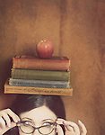 Partial face of a young woman wearing vintage glasses and blancing four books and an apple on her head