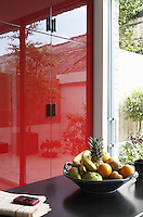 The red lacquer effect of the bespoke kitchen cupboards brings a sense of warmth to this contemporary kitchen