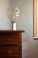 Wildflowers in a vase on a commode in a room. Tuscany, Italy