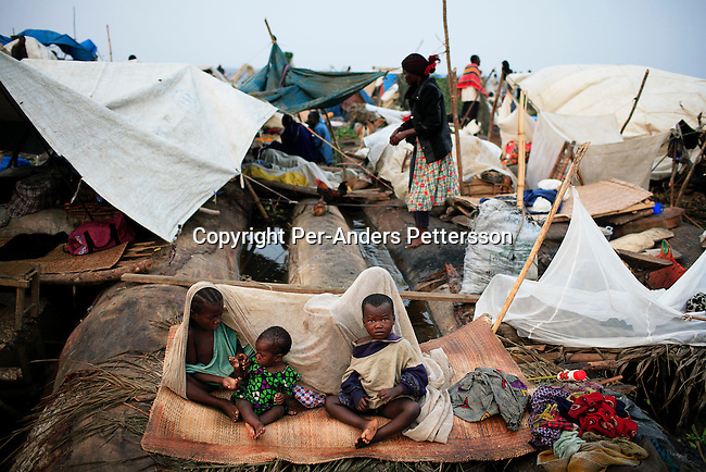 MBANDAKA, DEMOCRATIC REPUBLIC OF CONGO JUNE 29: Unidentified children wake up in the morning while traveling on a boat made of big trees on the Congo River on June 29, 2006 outside Mbandaka, Congo, DRC. The boat traveled with about 150 passengers from Bumba to Kinshasa, a journey of about 1300 kilometers. The traveled with their mother from a small rural village outside Bumba to the capital, Kinshasa. The Congo River is a lifeline for millions of people, who depend on it for transport and trade. Passengers slept in the open, with their goats, pigs and other animals. Boat travel is the only option for most people along the river as there?s no roads or infrastructure. Very few can afford to fly in a plane to the capital Kinshasa. During the Mobuto era, big boats run by the state company ONATRA dominated the river. These boats had cabins and restaurants etc. All the boats are now private and are mainly barges that transport goods. The crews sell tickets to passengers who travel in very bad conditions. The conditions on the boats often resemble conditions in a refugee camp. Congo is planning to hold general elections by July 2006, the first democratic elections in forty years. The Congolese and the international community are hoping that Congo will finally have piece and the country will be rebuilt..(Photo by Per-Anders Pettersson/Getty Images).