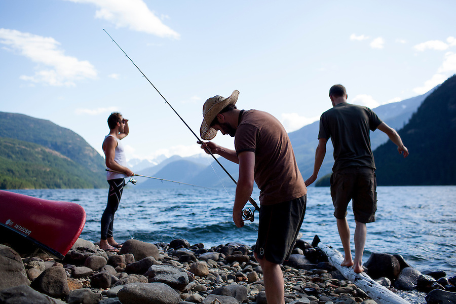 Three men fish off the shores of the Ponderosa Campground at Ross Lake, WA, USA.
