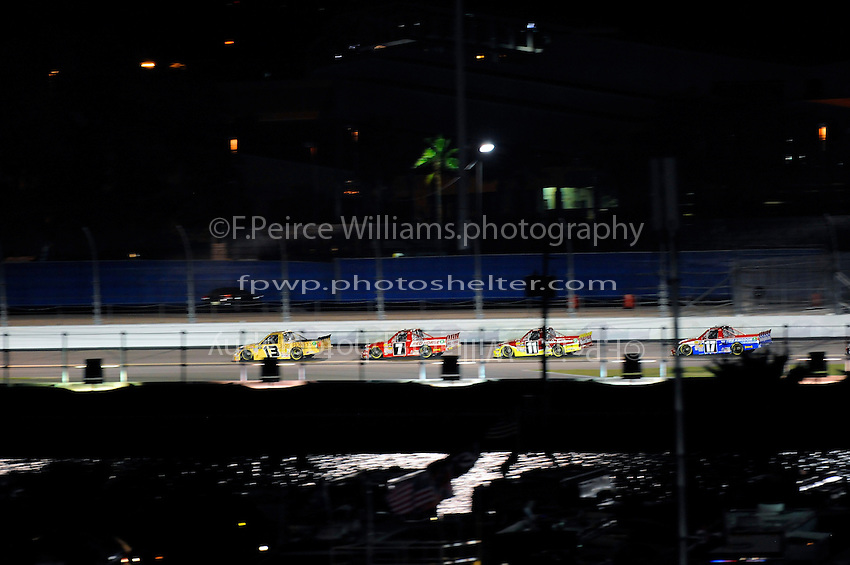 Johnny Sauter (#13), John King (#7), Todd Bodine (#11) and Timothy Peters (#17) race up the back straight.