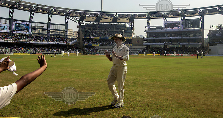 Sachin Tendulkar waves at fans while fielding at his 200th (and last) test cricket match before his retirement at Wankhede Stadium in Mumbai.